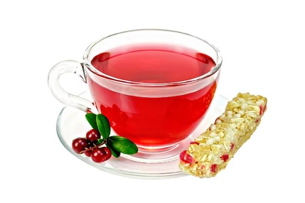 Chá em um copo de vidro, frutas vermelhas e folhas verdes, cranberries, barra de granola isolada no fundo branco