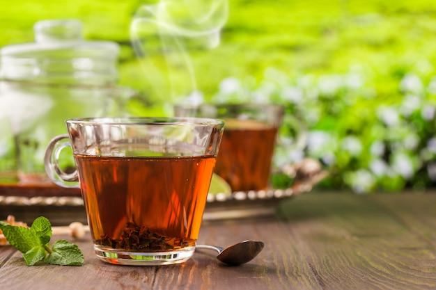 Chá em um copo de vidro sobre a mesa de madeira e o fundo das plantações de chá