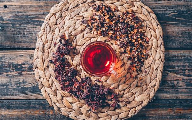 Chá em um trivet com vista superior de ervas de chá em um fundo escuro de madeira