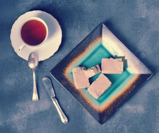 Chá em uma caneca com uma borda dourada e um pires e halva cortados em pedaços