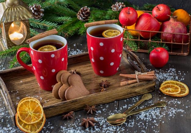 Chá em uma caneca com uma decoração de malha vermelha, uma lanterna, fatias de laranja, cesto de frutas, canela, ramos de abeto e biscoitos em forma de coração