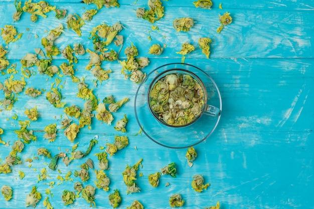 Chá em uma caneca de vidro com vista superior de ervas secas em madeira azul