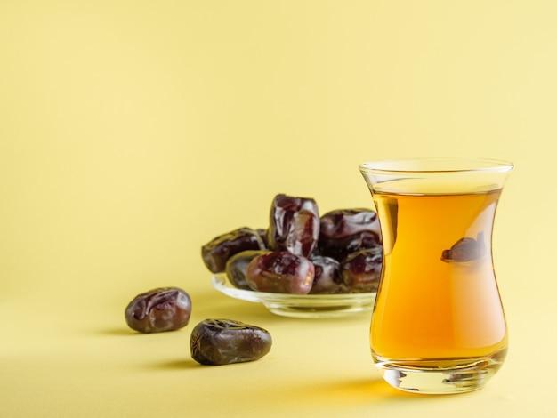 Chá em uma caneca tradicional turca com tâmaras. comida iftar tradicional durante o ramadã.