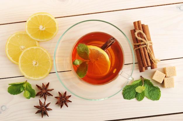 Chá em uma caneca transparente com folhas de limão, canela e hortelã