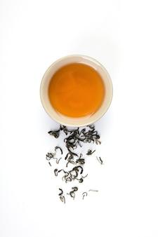 Chá em uma xícara e bule no fundo branco