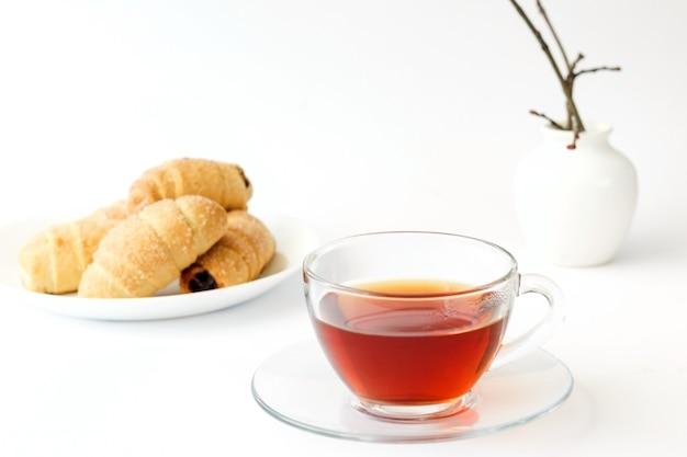 Chá em uma xícara transparente e croissants caseiros com geleia e uma planta isolada no fundo branco