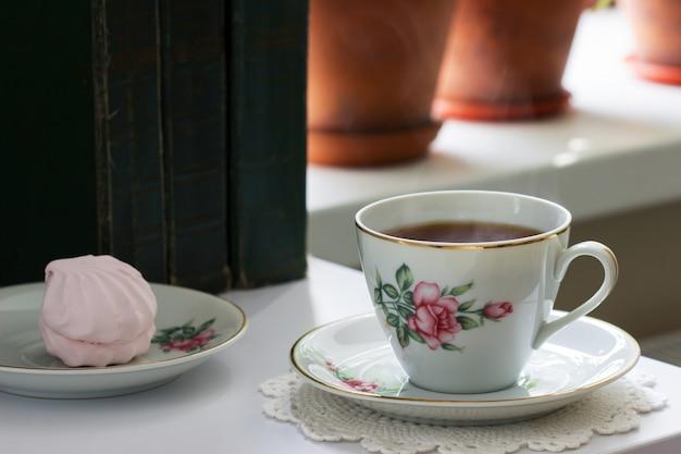 Chá em uma xícara vintage, marshmallows em um pires vintage e livros antigos sobre um fundo claro.