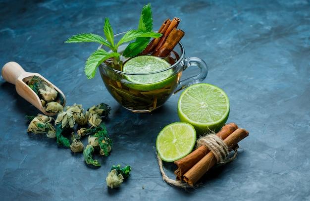 Chá em xícara com hortelã, canela, ervas secas, limão na superfície azul suja, vista de alto ângulo.