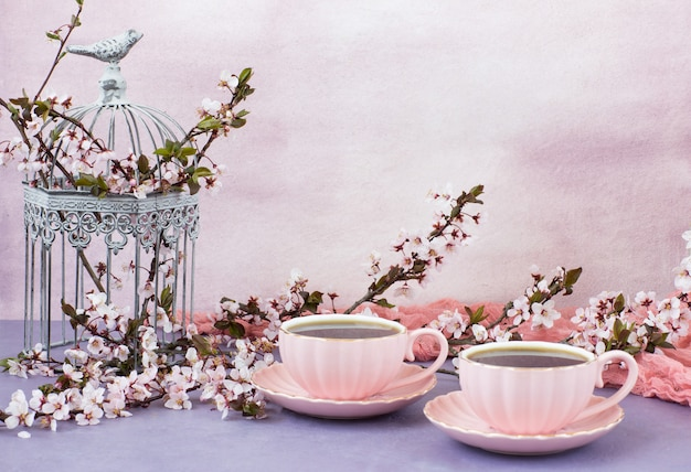 Chá em xícaras cor de rosa e flores de cerejeira em uma gaiola decorativa