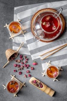 Chá feito de pétalas de rosa em copos e uma jarra