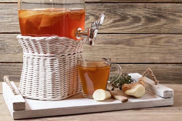 Chá fresco caseiro fermentado de kombuchá em uma jarra com torneira e em uma xícara