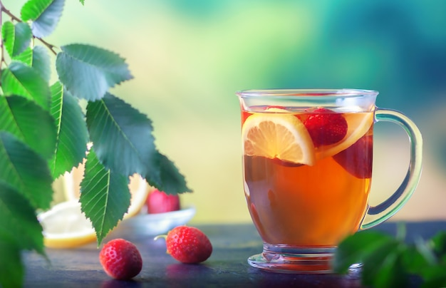 Chá fresco com limão e morangos em uma grande xícara de vidro