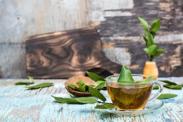 Chá fresco da folha de louro em um copo em uma tabela rústica de madeira. espaço da cópia