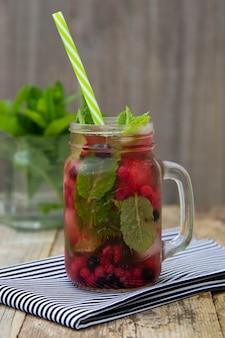 Chá fresco da fruta do gelo no frasco de pedreiro com palha. bebida de chá de frutas de verão, fundo de madeira