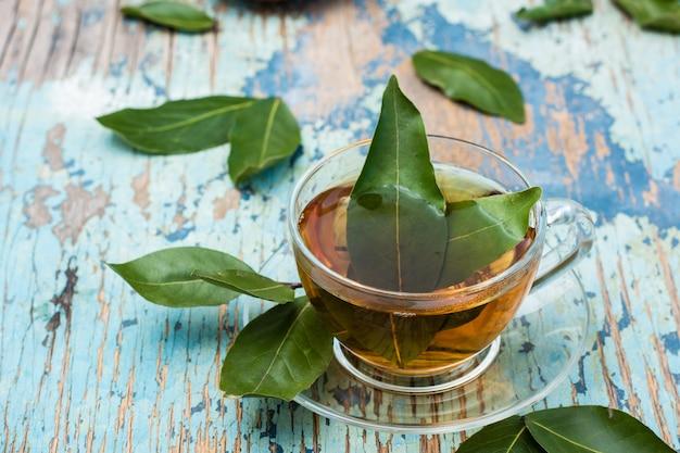 Chá fresco de folha de louro em um copo em uma mesa rústica de madeira