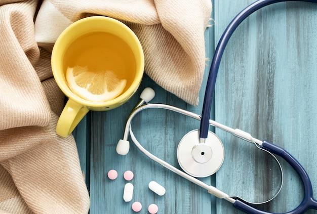 Chá frio, comprimidos, lenço de malha e estetoscópio.