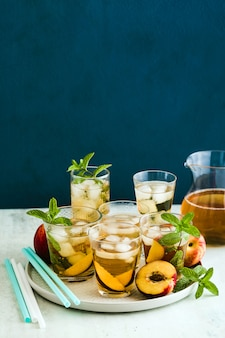 Chá frio de verão com pêssego e hortelã em copos em cima da mesa