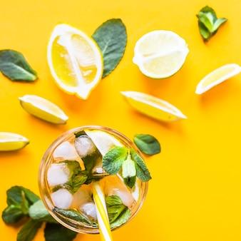 Chá gelado com gelo, limão e hortelã em um fundo amarelo colorido combinado