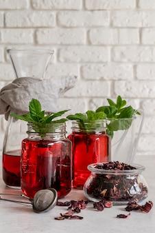 Chá gelado com hortelã e copo de frutas na mesa