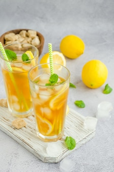 Chá gelado com limão, açúcar mascavo, folhas de hortelã e cubos de gelo em um copo sobre uma placa sobre um fundo claro. bebida refrescante de verão.