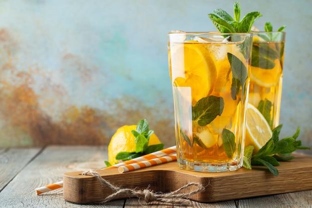 Chá gelado com limão e gelo em copos altos.