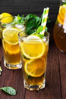 Chá gelado com limão e hortelã em um fundo de madeira