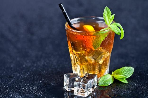 Chá gelado com limão, folhas de hortelã e cubos de gelo no vidro no fundo preto molhado.