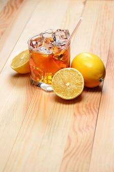 Chá gelado com limões em uma mesa de prancha de madeira