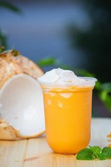 Chá gelado com smoothies de pedaços de coco na superfície de madeira