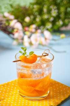 Chá gelado de limão caseiro de damasco de bebida fria de verão com cubos de gelo e hortelã.