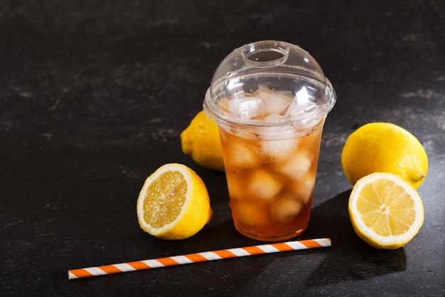 Chá gelado em copo de plástico com frutas frescas na mesa escura