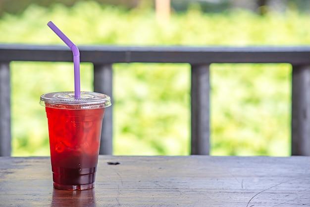 Chá gelado em um copo sobre a mesa de madeira.