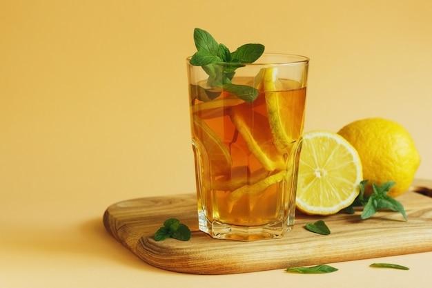 Chá gelado fresco e frio com limão e hortelã na superfície amarela