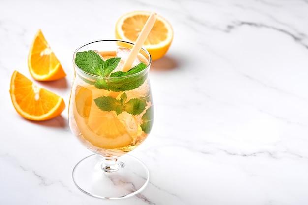 Chá gelado tradicional com limão e gelo em copos altos no fundo da mesa de mármore chá gelado com limão. foco seletivo. uma bebida refrescante de verão.