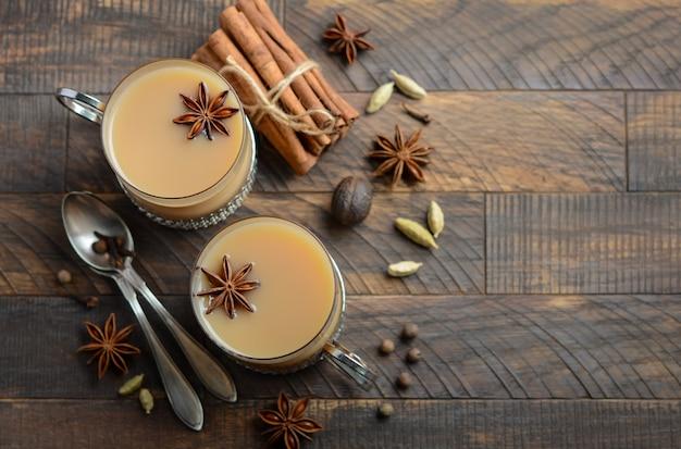 Chá indiano masala chai. chá com especiarias com leite nas xícaras vintage sobre o tabl de madeira rústica