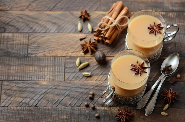 Chá indiano masala chai. chá temperado com leite em copos vintage na mesa de madeira rústica.