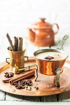 Chá indiano masala chai, chá temperado com leite em uma panela de cobre sobre superfície de madeira branca