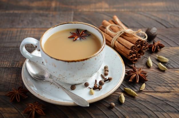 Chá indiano masala chai. chá temperado com leite na mesa de madeira rústica.
