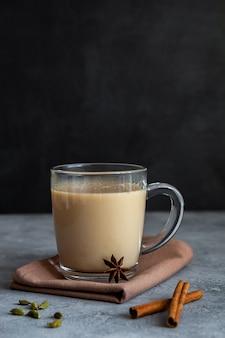Chá indiano masala chai com especiarias em uma caneca de vidro