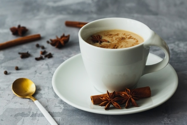 Chá indiano masala chai temperado com leite no fundo cinza de concreto