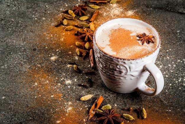 Chá indiano tradicional do masala chai com especiarias canela, cardamomo, anis, pedra escura. copyspace
