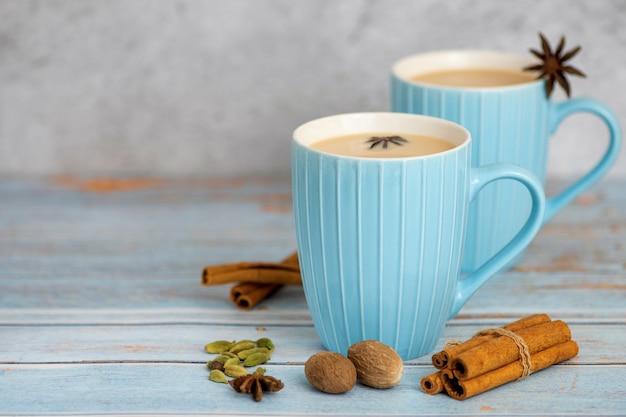 Chá indiano tradicional do masala chai na luz - copo azul com temperado.