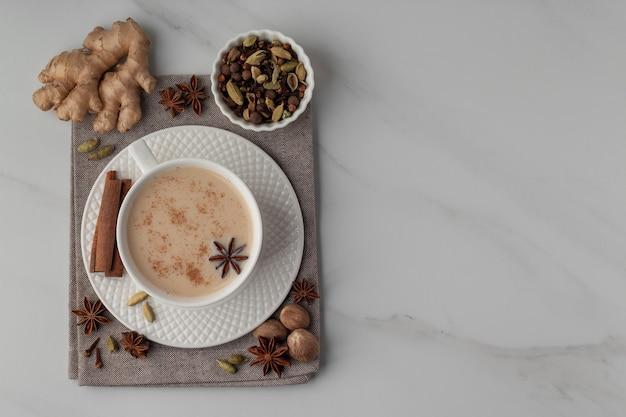 Chá indiano tradicional masala chai e especiarias em vista de mesa de mármore