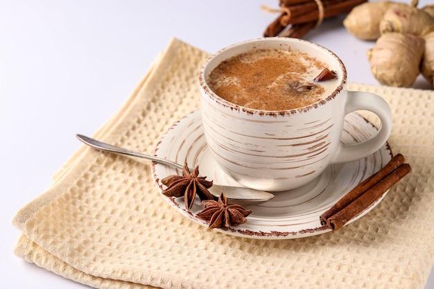 Chá indiano tradicional masala com especiarias em copo sobre uma superfície branca, formato horizontal, espaço de cópia