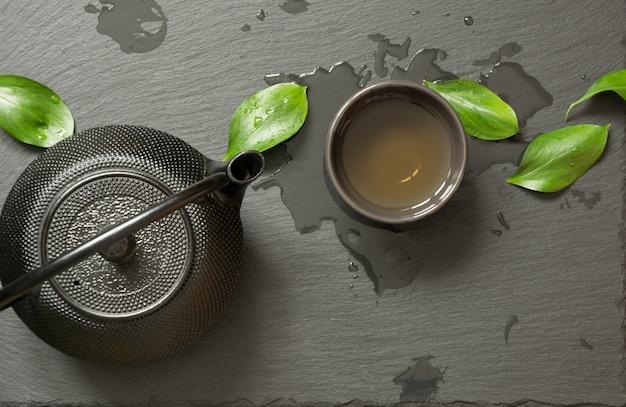 Chá japonês verde com bule de chá preto e tigela