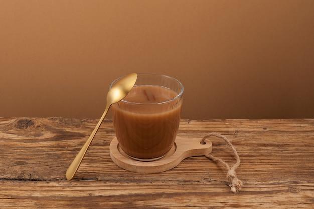 Chá karak ou masala chai na mesa de madeira vintage.