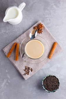 Chá masala chai. bebida tradicional indiana - chá masala com especiarias em fundo cinza.