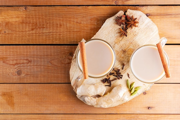 Chá masala chai em suporte de madeira. bebida tradicional indiana - chá masala com especiarias em um fundo de madeira.
