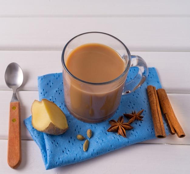 Chá masala chai em uma caneca, gengibre, paus de canela e anis