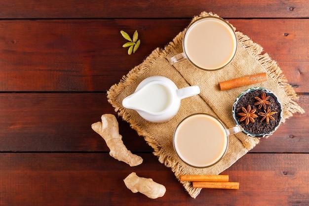 Chá masala chai na serapilheira. bebida tradicional indiana - chá masala com especiarias em um fundo de madeira.